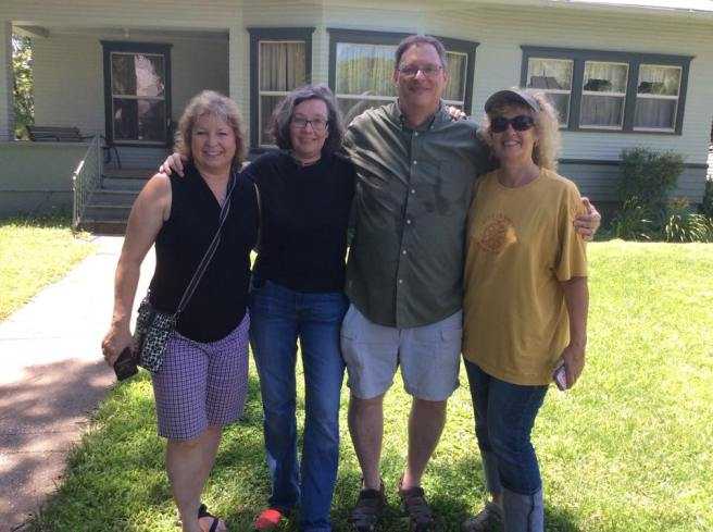 Laura, Elo, Art, and Linda in front of their grandmother's old house.